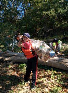 Caden picks up trash along the Ohio River (Photo: Fia Turczynewycz)