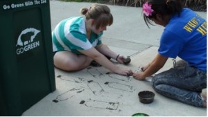 Amanda and Michelle create graffiti, using stencils and mud.