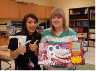 Amanda and Michelle show off their journals crafted out of an old dinosaur book.