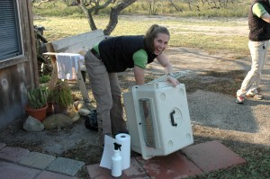 Wendy cleans the travel crate at the ranch.