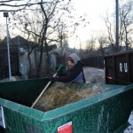 Paul scrapes off the waste that has frozen to the bin.