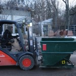 Paul moves a green bin for collecting waste.